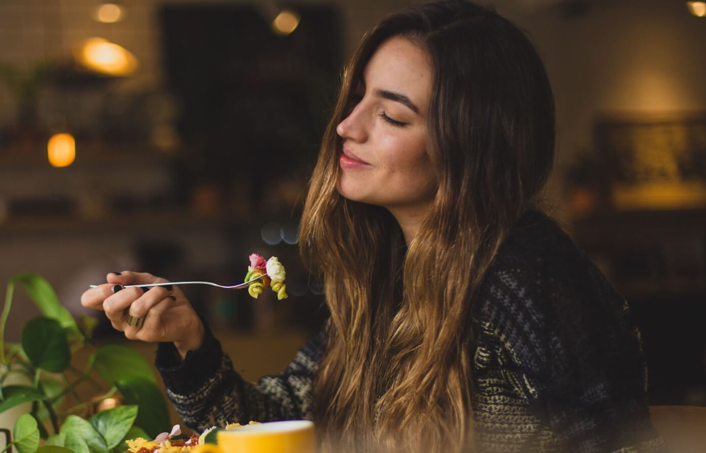 Savour your food. A woman enjoying their meal sitting at the table and smiling